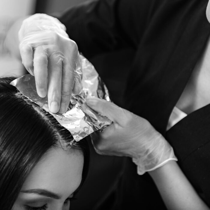 beauty concept, hairstylist holding foil on head of a client