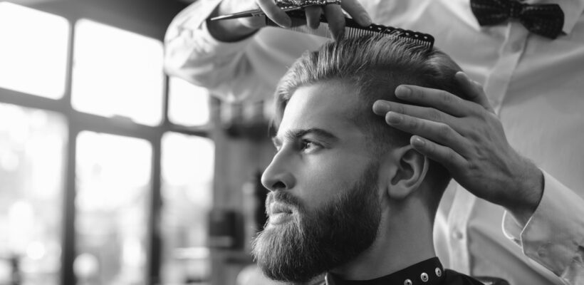 Young man sitting in a barbershop while barber cutting the hair