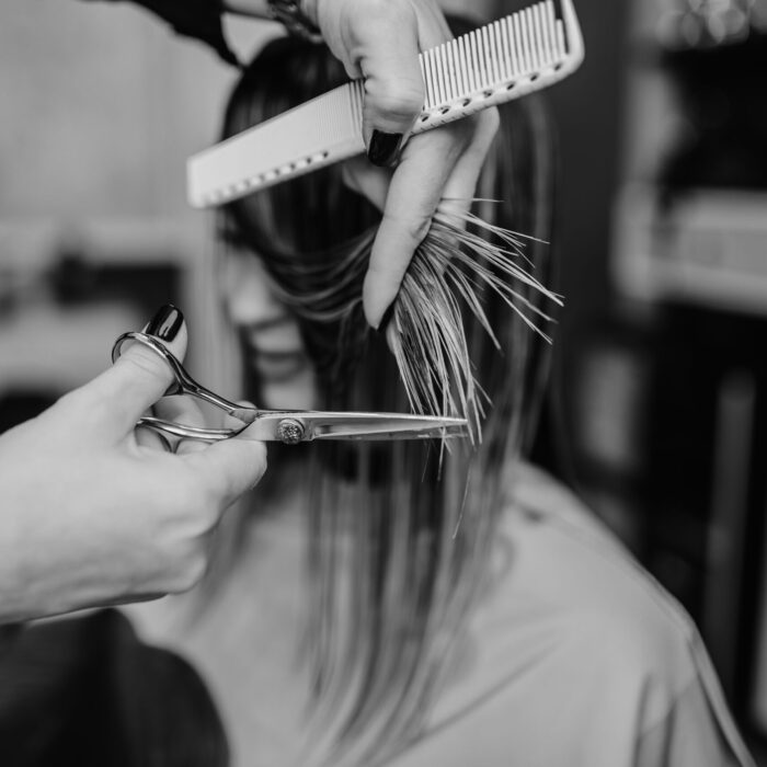 Beautiful young woman getting her haircut by a hairstylist at a beauty salon.